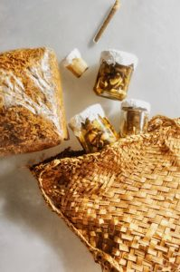 A traditional Maori Kete, or woven flax bag, spills out fungus-based food samples in small transparent containers.